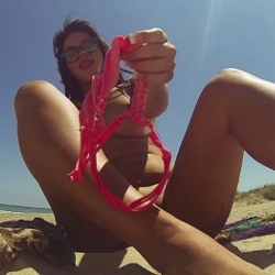 Tania fingers herself in a nude beach, surrounded by voyeurs.